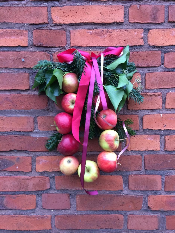 Krans af røde æbler md røde bånd tager i mod ved døren når det er jul